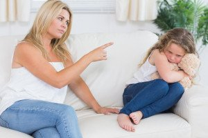 Angry mother scolding daughter clutchin teddy bear in living room